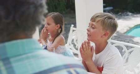 благодать : Over the shoulder view of Caucasian sibling enjoying their time with their family in a garden, sitting by a table, praying, in slow motion