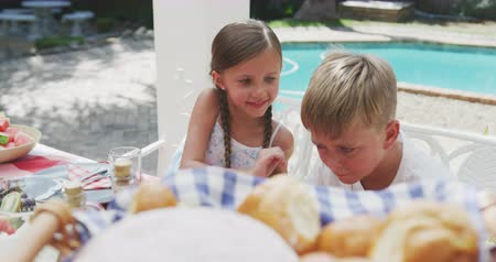 whispering : High angle view of Caucasian siblings enjoying time with their family in a garden, sitting by a table, a girl is whispering something into boys ear, in slow motion