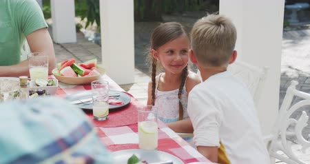 whispering : High angle view of Caucasian siblings enjoying time with their family in a garden, sitting by a table, a boy is whispering something into girls ear, in slow motion