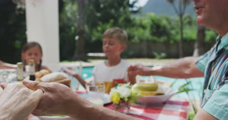 благодать : Side view close up of a multi-generation Caucasian family enjoying their time together in a garden, sitting by a table, saying grace, in slow motion