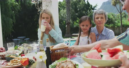 vodní meloun : Front view of a multi-generation Caucasian family enjoying their time together in a garden, sitting by a table, a senior man is putting a basket with bread down and passing a plate with watermelons to his partner, in slow motion