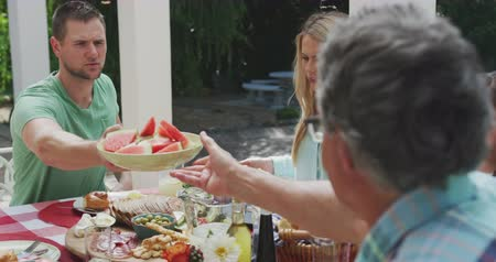 vodní meloun : Side view of a multi-generation Caucasian family enjoying their time together in a garden, sitting by a table, a senior man is passing a plate with watermelons to an adult man in slow motion