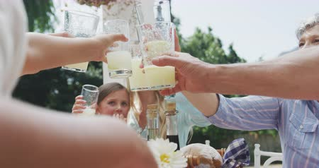 vychovávat : Side view close up of a multi-generation Caucasian family having a good time together, sitting in a garden, by a table with food on it, raising their glasses, making a toast, on a sunny day, in slow motion