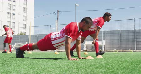 fotbal : Side view of a multi-ethnic group of male football players wearing a team strip, training at a sports field in the sun, doing push ups, running, in slow motion