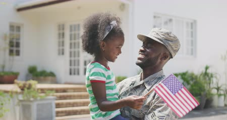 katonai : Front view of a happy African American man enjoying time in the garden, with his family, wearing military uniform, holding up his African American daughter holding a flag, on a sunny day, in slow motion