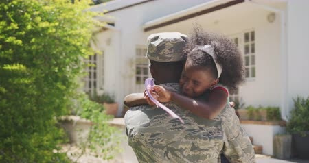 coming home : Rear view of an African American man enjoying time in the garden, with his family, wearing military uniform, holding up his crying African American daughter holding a flag, embracing, on a sunny day, in slow motion