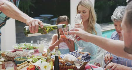 vodní meloun : Side view close up of a multi-generation Caucasian family having a good time together, sitting in a garden, by a table with food on it, a senior man is pouring wine to an adults man glass, on a sunny day, in slow motion Dostupné videozáznamy