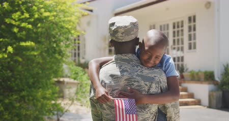 bandeira americana : Rear view of an African American man enjoying time in the garden, with his family, wearing military uniform, holding up his African American son holding a flag, embracing, on a sunny day, in slow motion