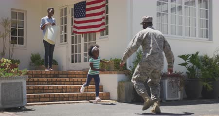 old glory : Rear view of an African American man enjoying time in the garden, with his family, wearing military uniform, returning home, with his partner and daughter holding a banner, with his daughter running towards him, embracing, with american flag in the backgr