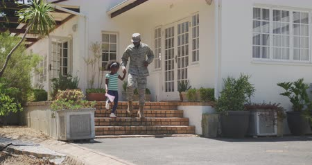 coming home : Front view of an African American man enjoying time in the garden, with his family, wearing military uniform, walking and holding hand of his African American daughter holding a flag, on a sunny day, in slow motion