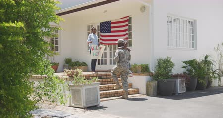 coming home : Side view of an African American man enjoying time in the garden, with his family, wearing military uniform, returning home, holding his daughter up, with his partner holding a banner, embracing, with american flag in the background, on a sunny day, in sl