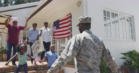 coming home : Rear view of an African American man enjoying time in the garden, with his family, wearing military uniform, returning home, with his multi-generation family greeting him, with his children running towards him, holding and waving american flags, on a sunn