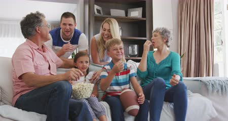 попкорн : Side view close up of a multi-generation Caucasian family enjoying their time in an apartment, sitting on a couch, smiling, watching a game, eating popcorn, celebrating, in slow motion