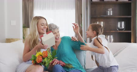 внучка : Front view of a Caucasian woman enjoying her time in an apartment, sitting on a couch, embracing and talking to her daughter and mother, giving flowers and a gift to her mother, in slow motion Стоковые видеозаписи