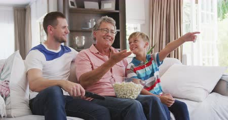 попкорн : Side view of a Caucasian man enjoying his time in an apartment, sitting on a couch with his son and father, watching tv, eating popcorn, holding a remote, in slow motion Стоковые видеозаписи