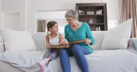 momento : Front view of a senior Caucasian woman enjoying her time in an apartment, sitting on a couch with her granddaughter, looking at family photos, in slow motion