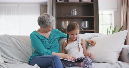 olgun : Front view of a senior Caucasian woman enjoying her time in an apartment, sitting on a couch with her granddaughter, reading a book, in slow motion Stok Video