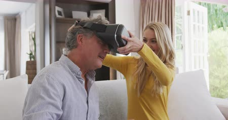behulpzaam : Side view of a senior Caucasian man enjoying his time in an apartment, sitting on a couch, with his daughter sitting by him, helping him to put a virtual reality headset on, in slow motion