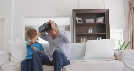 wizja : Front view of a senior Caucasian man enjoying his time in an apartment, sitting on a couch, with his grandson sitting by him, helping him to put a virtual reality headset on, in slow motion