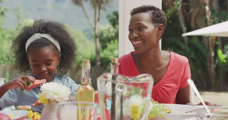 vodní meloun : Front view of an African American woman having a good time with her family, sitting by a table in a garden, talking, laughing, with her daughter sitting and eating a watermelon next to her, in slow motion Dostupné videozáznamy
