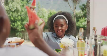 torcendo : Front view of an African American girl having a good time with her family, sitting by a table in a garden, doing a toast with watermelon pieces with her brother, on a sunny day, in slow motion