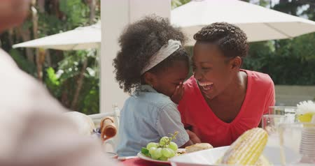 смущенный : Front view of an African American girl having a good time with her family, sitting by a table in a garden, whispering something into her mother ear, laughing, on a sunny day, in slow motion