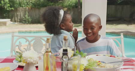 embarrassed : Front view of an African American girl having a good time with her family, sitting by a table in a garden, whispering something into her brother ear, laughing, on a sunny day, in slow motion Stock Footage