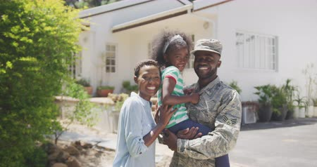 leisure time : Side view of an African American family enjoying time in the garden, a man is wearing military uniform, holding up his daughter, looking at the camera, on a sunny day, in slow motion