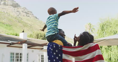 bandeira americana : Rear view of an African American family having a good time in a garden, standing, wrapped in the american flag, parents are holding their kids up, on a sunny day, in slow motion