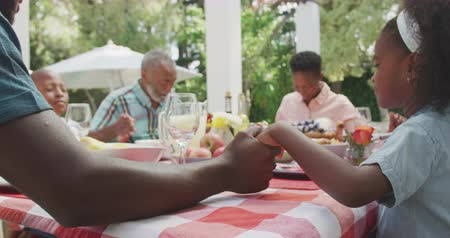 благодать : Side view of a multi-generation multi-ethnic family having a good time in a garden, sitting by a table with food on it, holding hands, saying grace on a sunny day, in slow motion
