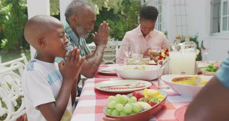 благодать : Side view of a multi-generation multi-ethnic family having a good time in a garden, sitting by a table with food on it, holding hands, praying, on a sunny day, in slow motion
