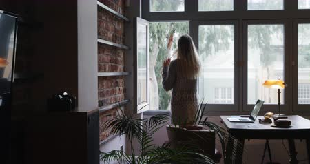 resting : Rear view of attractive Caucasian woman with long blond hair enjoying time at home, standing in her sitting room, texting on the smartphone and looking at the window.