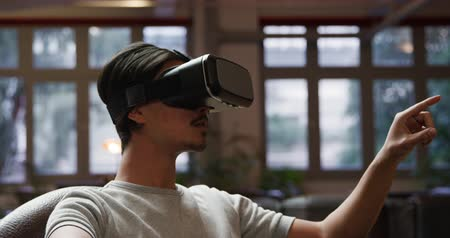 kısa : Front view of a mixed race man enjoying time at home, sitting on the couch in his sitting room, using VR goggles, touching virtual interactive screen with his finger. Stok Video