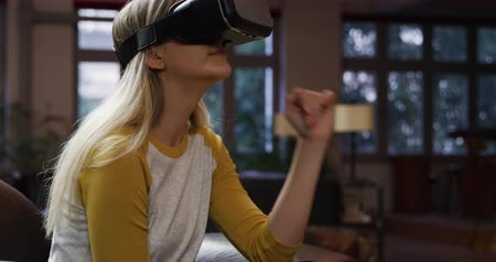 fejhallgató : Front view of attractive Caucasian woman with long blonde hair, enjoying time at home, sitting on the couch in her sitting room, using VR goggles.