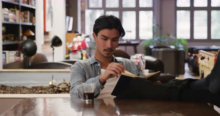 kısa : Front view of handsome mixed race man with short dark hair enjoying time at home, sitting with his feet up on a table in his sitting room, reading a book, cup of coffee next to him. Stok Video