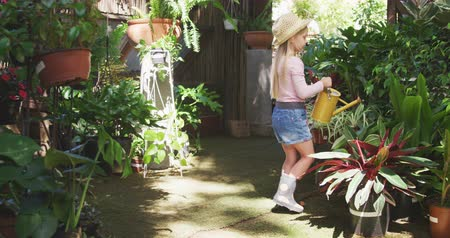 watering can : Side view of a Caucasian girl with long blonde hair enjoying time in a sunny garden, exploring, watering plants with watering can, wearing wellingtons and a hat, in slow motion