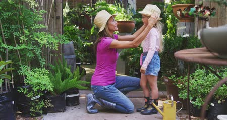 ajoelhado : Side view of a Caucasian woman and her daughter enjoying time together in a sunny garden, woman kneeling and putting hat on her daughters head, smiling to each other, both wearing wellingtons, in slow motion Vídeos