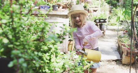 watering can : Front view of a Caucasian girl with long blonde hair enjoying time in a sunny garden, exploring, watering plants with watering can, wearing a hat, smiling to the camera, in slow morion Stock Footage