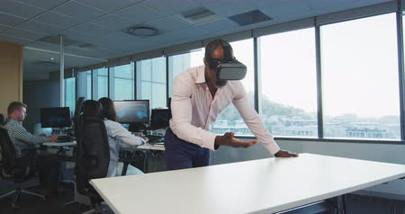 fejhallgató : Front view of an African American businessman working in a modern office, wearing Visual Reality headset, touching a virtual reality screen, with his colleagues working in the background in slow motion Stock mozgókép