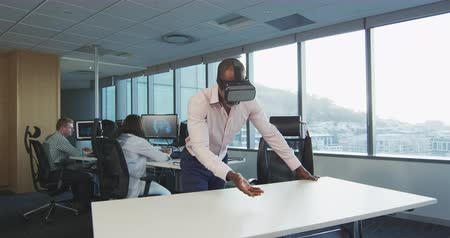 агентство : Front view of an African American businessman working in a modern office, wearing Visual Reality headset, touching a virtual reality screen, with his colleagues working in the background in slow motion Стоковые видеозаписи