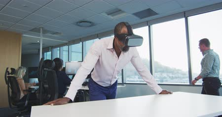 agentura : Front view of an African American businessman working in a modern office, wearing Visual Reality headset, with his colleagues working in the background in slow motion Dostupné videozáznamy