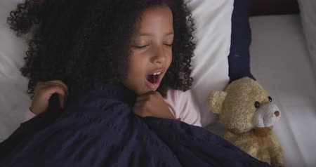 плюшевый мишка : High angle front view of a mixed race girl enjoying time at home, lying in bed, yawning, covering herself with a duvet, in slow motion Стоковые видеозаписи