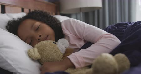 beer : Side view of a mixed race girl enjoying time at home, lying in bed, sleeping, smiling, hugging a teddy bear, in slow motion Stockvideo