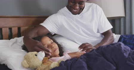 плюшевый мишка : Side view of an African American man and his mixed race daughter enjoying time at home together, a man is sitting on a bed, waking his daughter up, tickling her, in slow motion Стоковые видеозаписи