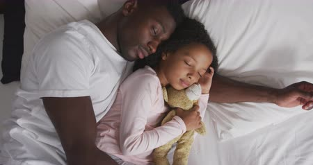 beer : High angle view of an African American man and his mixed race daughter enjoying time at home together, lying on a bed, sleeping together, a girl is holding a teddy bear, in slow motion