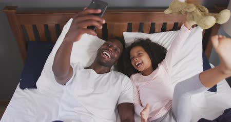 ursinho de pelúcia : High angle view of an African American man and his mixed race daughter enjoying time at home together, lying on a bed, girl is holding a teddy bear and a man is taking selfies, in slow motion