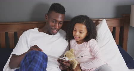 teddy bear : Front view of an African American man and his mixed race daughter enjoying time at home together, sitting on a bed, a man is reading his daughter a book, laughing, in slow motion