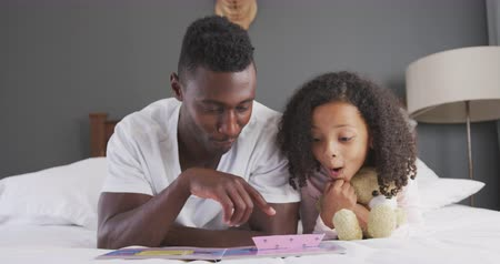плюшевый мишка : Front view of an African American man and his mixed race daughter enjoying time at home together, lying on a bed, a man is reading his daughter a book, laughing, in slow motion