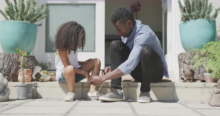 generation z : Side view of an African American man and his mixed race daughter enjoying time in front of the house together, a man is tying his daughters shoe, in slow motion