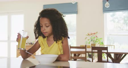 jídelna : Front view of a mixed race girl enjoying her time at home, sitting by a table, eating breakfast, drinking juice, in slow motion